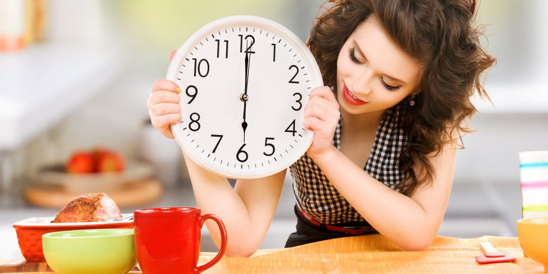 Woman holding clock over dinner table